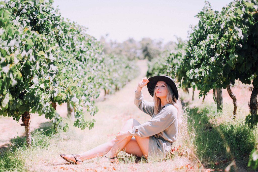 beautiful-blonde-girl-wearing-hat-enjoying-wine-to-M7QTMXX